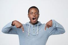 Afrikaan verraste en schokte klant die kijkt neer richtend wijsvinger hebben zich verbaasd stock foto's