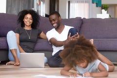 Afrikaans Amerikaans echtpaar die laptop met behulp van terwijl dochter het spelen stock foto's