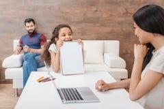Afrikaans Amerikaans meisje die tekeningsalbum erachter tonen aan haar moeder terwijl vaderzitting Stock Foto