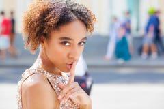 Afrikaans Amerikaans meisje of jonge vrouw die kleding met haar vinger op haar lippen dragen die om stilte vragen of een geheim h royalty-vrije stock foto's