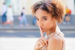 Afrikaans Amerikaans meisje of jonge vrouw die kleding met haar vinger op haar lippen dragen die om stilte vragen of een geheim h stock afbeeldingen
