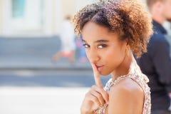 Afrikaans Amerikaans meisje of jonge vrouw die kleding met haar vinger op haar lippen dragen die om stilte vragen of een geheim h royalty-vrije stock foto
