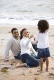 Afrikaans-Amerikaans meisje met ouders op strand stock fotografie