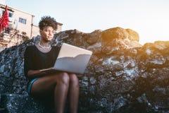 Afrikaans Amerikaans niet-gegradueerdenmeisje met netbook openlucht royalty-vrije stock fotografie