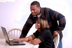 Afrikaans-Amerikaans paar dat de computer bekijkt royalty-vrije stock afbeeldingen