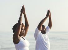 Afrikaans Amerikaans paar die bij het strand uitwerken stock afbeelding