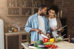 Afrikaans-Amerikaans paar die recept bekijken die digitale tablet gebruiken stock afbeelding