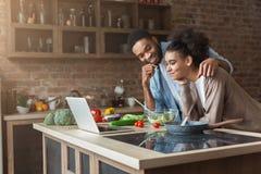 Afrikaans-Amerikaans paar kokend diner met recept op laptop stock afbeelding