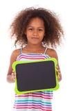 Afrikaans Amerikaans schoolmeisje die een lege zwarte raad houden - Zwarte royalty-vrije stock foto