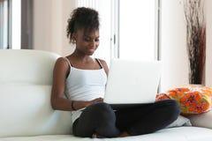 Afrikaans Amerikaans studentenmeisje die een laptop computer met behulp van - zwarte pe stock fotografie