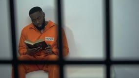 Afrikaans-Amerikaanse gevangene die heilige bijbel, veroordeelde zondaar, godsdienst lezen stock video