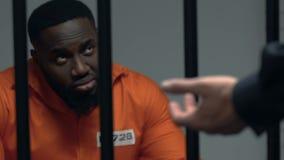 Afrikaans-Amerikaanse gevangene die op wacht met knuppel in handen kijken, straf stock video