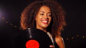 Afrikaans-Amerikaanse jonge vrouw in partijkleding die vinylverslag houden en op zwarte lichtenachtergrond dansen Het glimlachen