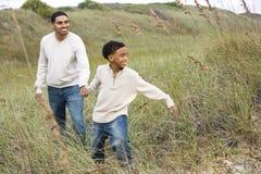 Afrikaans-Amerikaanse jongen die vader op zandduinen trekt royalty-vrije stock fotografie
