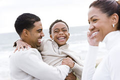Afrikaans-Amerikaanse jongen en ouders die op strand lachen stock afbeeldingen