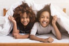 Afrikaans-Amerikaanse kindmeisjes die onder deken op bed liggen royalty-vrije stock foto's