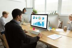 Afrikaans-Amerikaanse manager die met binnen statistieken aan computer werken royalty-vrije stock foto's