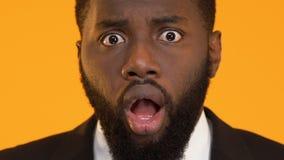 Afrikaans-Amerikaanse mens in kostuum die door slecht nieuws, ontbroken bedrijfsproject wordt verbaasd stock videobeelden