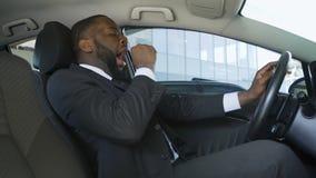 Afrikaans-Amerikaanse mens in kostuumzitting in auto en geeuw, bestuurder van zakenman stock footage