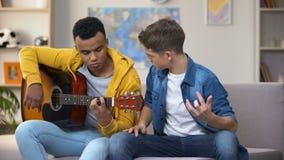 Afrikaans-Amerikaanse tiener die Kaukasische vriend onderwijzen om gitaar, hobby te spelen stock footage