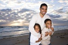 Afrikaans-Amerikaanse vader en twee kinderen op strand Stock Foto
