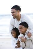Afrikaans-Amerikaanse vader en twee kinderen op strand stock foto's
