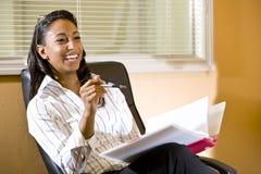 Afrikaans-Amerikaanse vrouw in bureau dat nota's neemt Royalty-vrije Stock Afbeeldingen