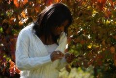 Afrikaans-Amerikaanse vrouw die bij bladeren staart royalty-vrije stock foto's