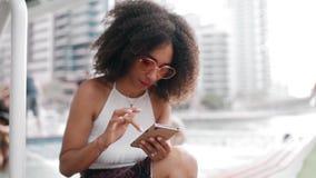 Afrikaans-Amerikaanse vrouw die mobiele telefoon openlucht in de stad met behulp van stock video