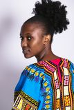 Afrikaans meisje in blauwe omgeslagen kleding en kijkend stock afbeeldingen