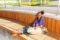 Afrikaans van de meisjeszitting en holding skateboard Royalty-vrije Stock Afbeeldingen