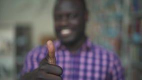 Afrikaanse Amerikaan toont grote vinger aan de camera in bibliotheek stock footage