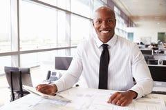 Afrikaanse Amerikaanse architect aan werk, die aan camera het glimlachen Royalty-vrije Stock Foto