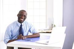Afrikaanse Amerikaanse architect die met computer en blauwdrukken in bureau werken stock foto