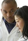 Afrikaanse Amerikaanse arts die met Vrouwelijke Aziatische arts spreken royalty-vrije stock foto