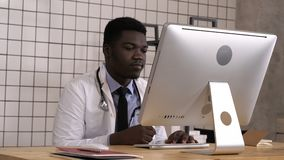 Afrikaanse Amerikaanse arts die op het werk monitor van zijn computer bekijken stock video