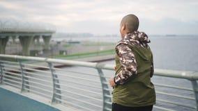 Afrikaanse Amerikaanse atleet die langzaam op brug op stedelijk gebied lopen stock video