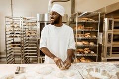 Afrikaanse Amerikaanse bakker die ruw deeg voor gebakje voorbereiden stock afbeeldingen