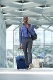 Afrikaanse Amerikaanse bedrijfsmens die bij luchthaven met bagage lopen royalty-vrije stock foto