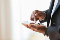 Afrikaanse Amerikaanse bedrijfsmens die een tastbare tablet over wit gebruiken Stock Afbeelding