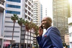 Afrikaanse Amerikaanse bedrijfsmens die op mobiele telefoon in de stad spreken Royalty-vrije Stock Foto