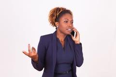 Afrikaanse Amerikaanse bedrijfsvrouw die een telefoongesprek maken Stock Foto