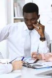 Afrikaanse Amerikaanse die zakenman op vergadering in bureau, in wit wordt gekleurd Onderhandeling of hard besluitconcept royalty-vrije stock fotografie