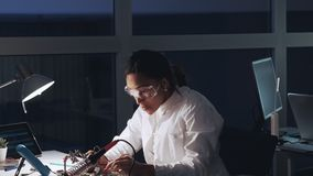 Afrikaanse Amerikaanse elektronikaspecialist in beschermende glazen en witte laag die met multimetermeetapparaat werken en stock footage