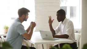 Afrikaanse Amerikaanse en Kaukasische zakenlieden die handenschudden over bureau bespreken stock footage