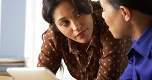 Afrikaanse Amerikaanse en Spaanse bedrijfsvrouwen die tabletcomputer met behulp van Stock Foto