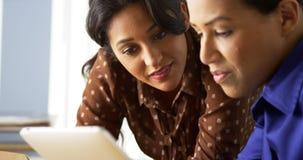 Afrikaanse Amerikaanse en Spaanse onderneemsters die tabletcomputer met behulp van royalty-vrije stock fotografie
