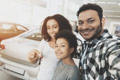Afrikaanse Amerikaanse familie bij het autohandel drijven De moeder, de vader en de zoon nemen selfie met sleutels voor nieuwe au stock fotografie