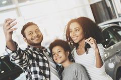 Afrikaanse Amerikaanse familie bij het autohandel drijven De moeder, de vader en de zoon nemen selfie voor nieuwe auto royalty-vrije stock foto's