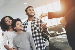 Afrikaanse Amerikaanse familie bij het autohandel drijven De verkoper geeft sleutels voor nieuwe auto stock afbeelding